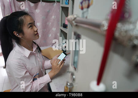 (190518) -- NANJING, May 18, 2019 (Xinhua) -- Zhou Wenqing 'reads' an article by her mobile phone in her dormitory at Nanjing Normal University of Special Education in Nanjing, east China's Jiangsu Province, May 17, 2019. Wu Yifan, 22, and Zhou Wenqing, 21, are schoolmates in Nanjing Normal University of Special Education. Both of them lost eyesight in their childhood.   In their spare time, Wu likes doing makeup, paper-cutting as well as playing the Guzheng, Chinese Zither. While Zhou enjoys playing the piano. Zhou once developed a computer game for visually impaired people.   The two girls h - Stock Photo