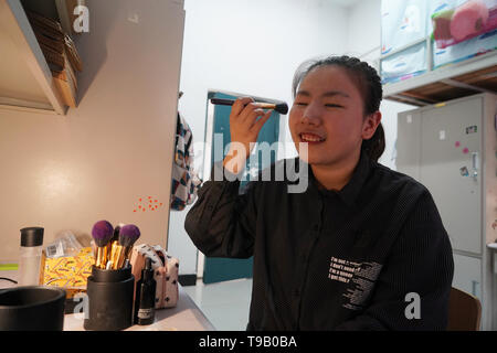 (190518) -- NANJING, May 18, 2019 (Xinhua) -- Wu Yifan does her own makeup in her dormitory of Nanjing Normal University of Special Education in Nanjing, east China's Jiangsu Province, May 17, 2019. Wu Yifan, 22, and Zhou Wenqing, 21, are schoolmates in Nanjing Normal University of Special Education. Both of them lost eyesight in their childhood.   In their spare time, Wu likes doing makeup, paper-cutting as well as playing the Guzheng, Chinese Zither. While Zhou enjoys playing the piano. Zhou once developed a computer game for visually impaired people.   The two girls have passed the College  - Stock Photo