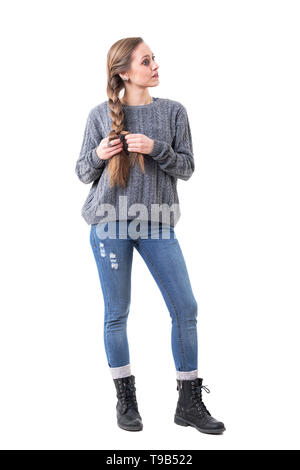 Thoughtful introspective young woman making hair braids looking away. Full body isolated on white background. - Stock Photo