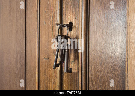Old rusty keys inside a keyhole of an old antique closet. vintage design - Stock Photo