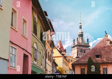 View towards the centre of Sighisoara citadel with the Clock Tower and colorful houses on a sunny day.