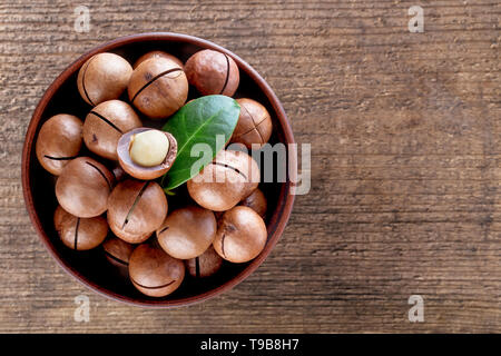 Australian macadamia nuts with leaf in plate - Stock Photo