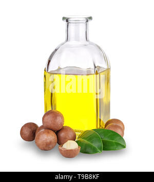 Macadamia oil in bottle and nuts - Stock Photo