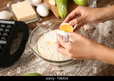 Woman making dough for squash waffles on wooden table - Stock Photo