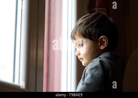 Baby boy looking through glass window