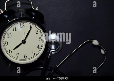 Alarm clock, stethoscope on black background. With education, medical and health concepts - Stock Photo