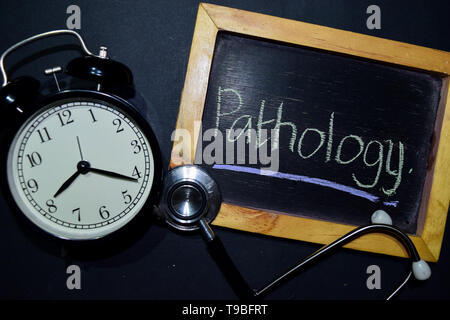 The words Pathology handwriting on chalkboard on top view. Alarm clock, stethoscope on black background. With education, medical and health concepts - Stock Photo