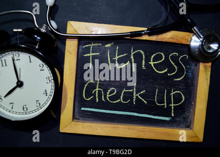 The words Fitness Check up handwriting on chalkboard on top view. Alarm clock, stethoscope on black background. With education, medical and health con - Stock Photo