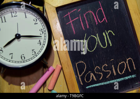 Find Your Passion on phrase colorful handwritten on chalkboard and alarm clock with motivation, inspiration and education concepts. Table background - Stock Photo