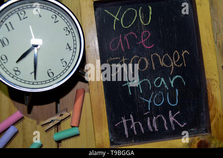 You Are Stronger Than You Think on phrase colorful handwritten on chalkboard and alarm clock with motivation, inspiration and education concepts. Tabl - Stock Photo