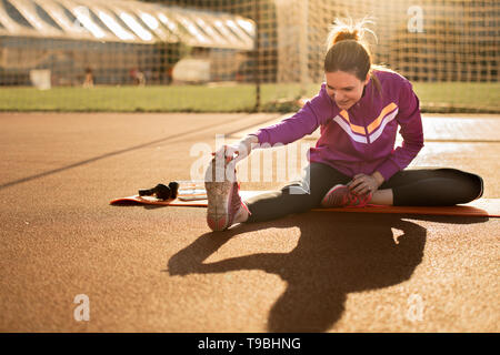 Young sporty woman doing exercises on mat on a sunny day