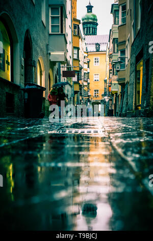 Street scene on rainy day in Innsbruck Austria with old architecture, puddles, reflections, umbrellas and unrecognizable people - Stock Photo