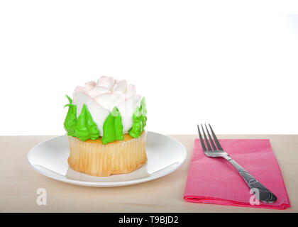 Large cup cake with giant frosting rose sitting on white plate on wood table, pink napkin with fork. Simple design with copy space for Mother's Day, V - Stock Photo
