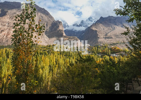 Beautiful scenery panoramic view in Hunza valley. Nature landscape of lush green forest with clouds covered snow capped Ultar Sar mountain in Karakora - Stock Photo