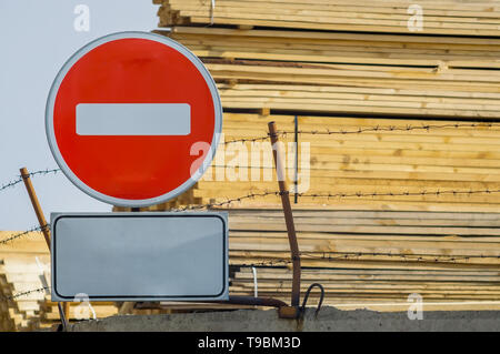 sign, symbol, warning about the prohibition of entry to the territory of the industrial zone with building materials, lumber, placed on the fence - Stock Photo
