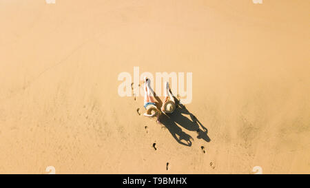 Aerial view with couple of beautiful young girls enjoyimg the beach like tourists in summer holiday vacation leisure activity - nice shadow on the flo - Stock Photo