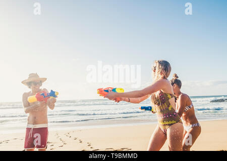 People having fun in sunny day of summer holiday vacation at the beach with water guns - friends play and laugh a lot - tourism and travel to ocean re - Stock Photo