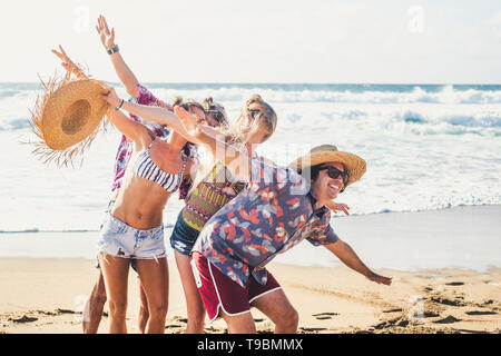 Summer style group of young cheerful people together having fun and laughina a lot in holiday vacation at the beach - sea waves and blue sky in backgr - Stock Photo