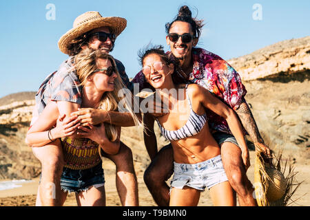 Group of young cheerful happy millennial people in outdoor leisure activity playing together like friends and having a lot of fun laughing and smiling - Stock Photo