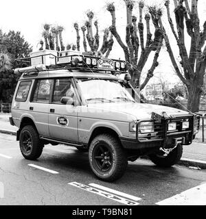 Strasbourg, France - Dec 27, 2017: Square image of new vintage yellow Land Rover Defender Camel Trophy with luggage on the roof parked in central city street black and white - Stock Photo