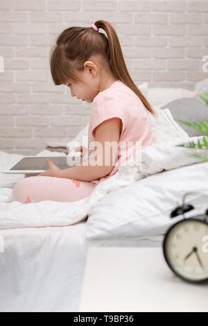 cute little child girl lies in bed uses digital tablet. child playing on tablet pc. - Stock Photo