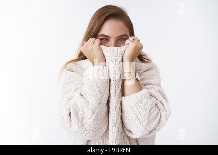 Enthusiastic charismatic good-looking girlfriend playing boyfriend hiding face sweater collar pulling cloth nose smiling eyes giggling having fun - Stock Photo