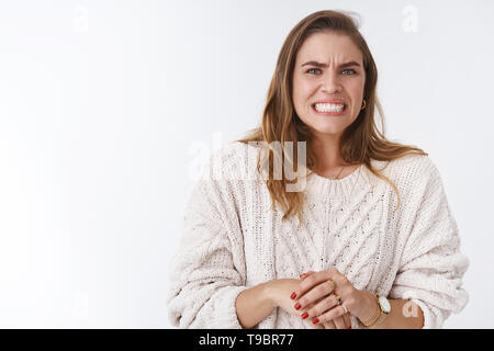 Woman feeling awkward intense feeling problems, making huge mistake worrying grimacing wrinkle nose clenching teeth stooping guilty, nervously - Stock Photo