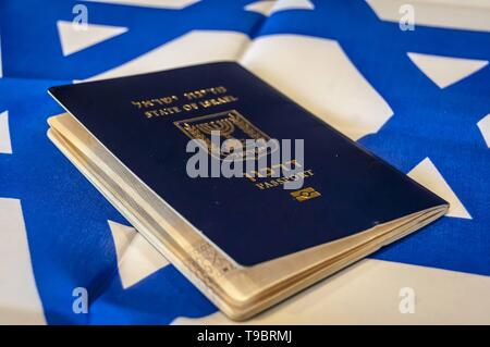 A blue passport of the State of Israel on Israeli flag on the background. Israel citizenship concept, Israeli biometric 'darkon' passport illustrative - Stock Photo
