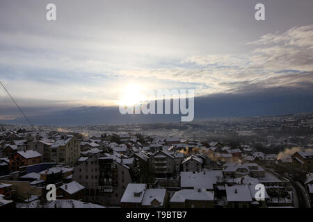 Beautiful view of winter morning fog, snow and sun filling on landscape of houses and buildings in Belgrade. Scenery during sunrise, sunset top view. - Stock Photo