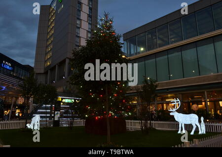 London/United Kingdom - December 15, 2014: Phosphorescent deers walking around Christmas tree installed in Westfield Stratford City shopping centre. - Stock Photo