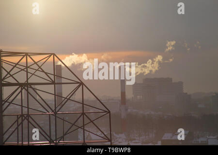 Smoking from industrial chimneys of heating plant emits smoke, smog at sunset in city, pollutants enter atmosphere. Environmental disaster. - Stock Photo