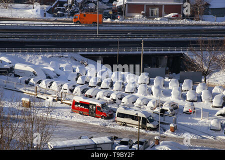 Cars on parking and street covered with big snow layer. View of winter and snowing on city street with snowflakes. In snowy season, motor vehicles. - Stock Photo