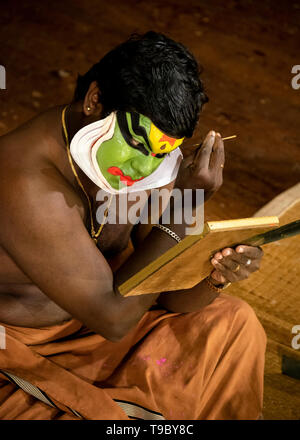 Vertical aerial view of the lead Kathakali performer putting on the distinctive green make up in Kerala, India. - Stock Photo