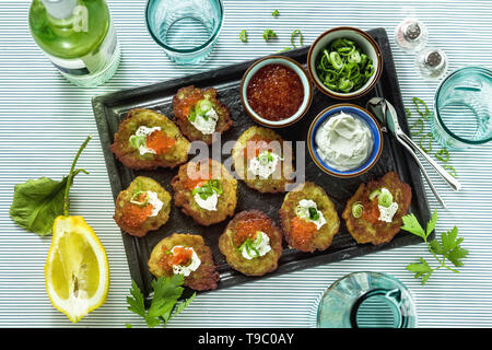 Russian traditional potato pancakes served with red caviar, green onions and sour cream on a tray with white wine and lemon - Stock Photo