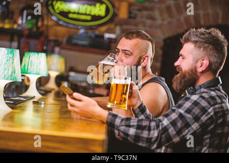 Men drinking beer together. Hipster brutal man drinking beer with friend at bar counter. Men drunk relaxing having fun. Alcohol drinks. Friends relaxing in pub with beer. Refreshing beer concept. - Stock Photo