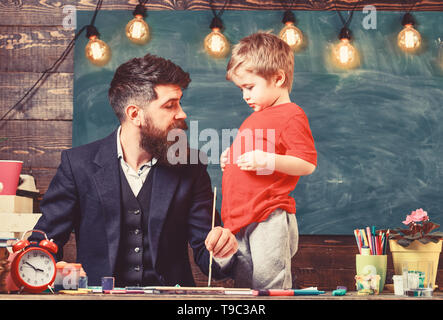 Fatherhood concept. Teacher with beard, father teaches little son to draw in classroom, chalkboard on background. Talented artist spend time with son. Child calm and teacher painting, drawing.
