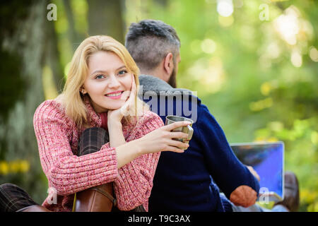 He is workaholic. Happy loving couple relaxing in park with laptop. Man freelance worker internet addicted gamer with laptop forest. Internet addicted husband. Working on fresh air. Surfing internet. - Stock Photo