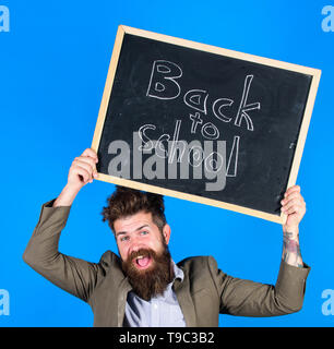 Stay positive. Teacher bearded man holds blackboard with inscription back to school blue background. Teacher with tousled hair cheerful about school year beginning. Keep working and be kind to people. - Stock Photo