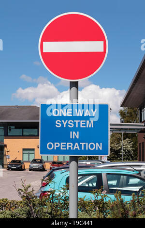 Bright Red and white 'No Entry' sign with white on blue 'One Way System in Operation' sign in an office car park - Stock Photo