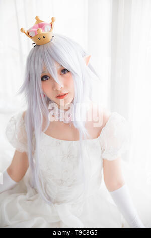 Portrait of vampire dracula young woman dress in white tone room halloween concept - Stock Photo
