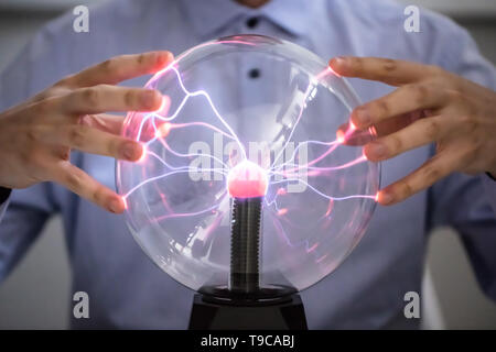 Close-up Of Fortune Teller Holding Hand Over The Glowing Crystal Ball - Stock Photo