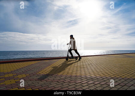 Adult man on an electric scooter on the embankment near the sea at sunset, looking into the distance, silhouette, free space - Stock Photo