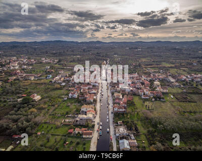 Aerial drone shot of a small town called Lefkimmi in South Corfu Greece.River running through. - Stock Photo