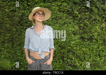 Portrait of a beautiful female traveler. Smiling young woman in summer hat wearing sunglasses, standing in front of lush tropical plant greenery wall - Stock Photo