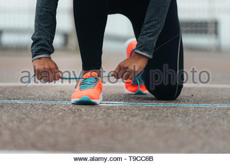 Detail of sporty swman lacing running shoes before before training. Outdoor city workout concept. Female fitness athlete getting ready for working out - Stock Photo