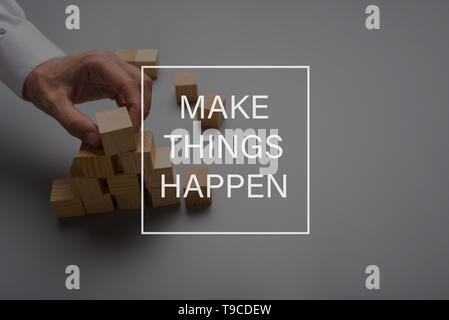 Make things happen sign in front of a male hand assembling a pyramid of wooden blocks. - Stock Photo
