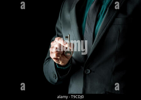 Close-up of incognito man in black suite, holding vintage key with two fingers, standing isolated on black background. - Stock Photo