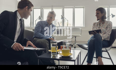 Three business people sitting around a coffee table in an office having a meeting. - Stock Photo