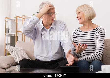 Mature Couple Calculating Bills, Discussing Home Economics - Stock Photo