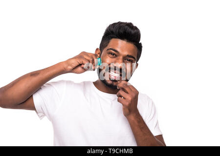 Man flossing his teeth isolated on white background - Stock Photo